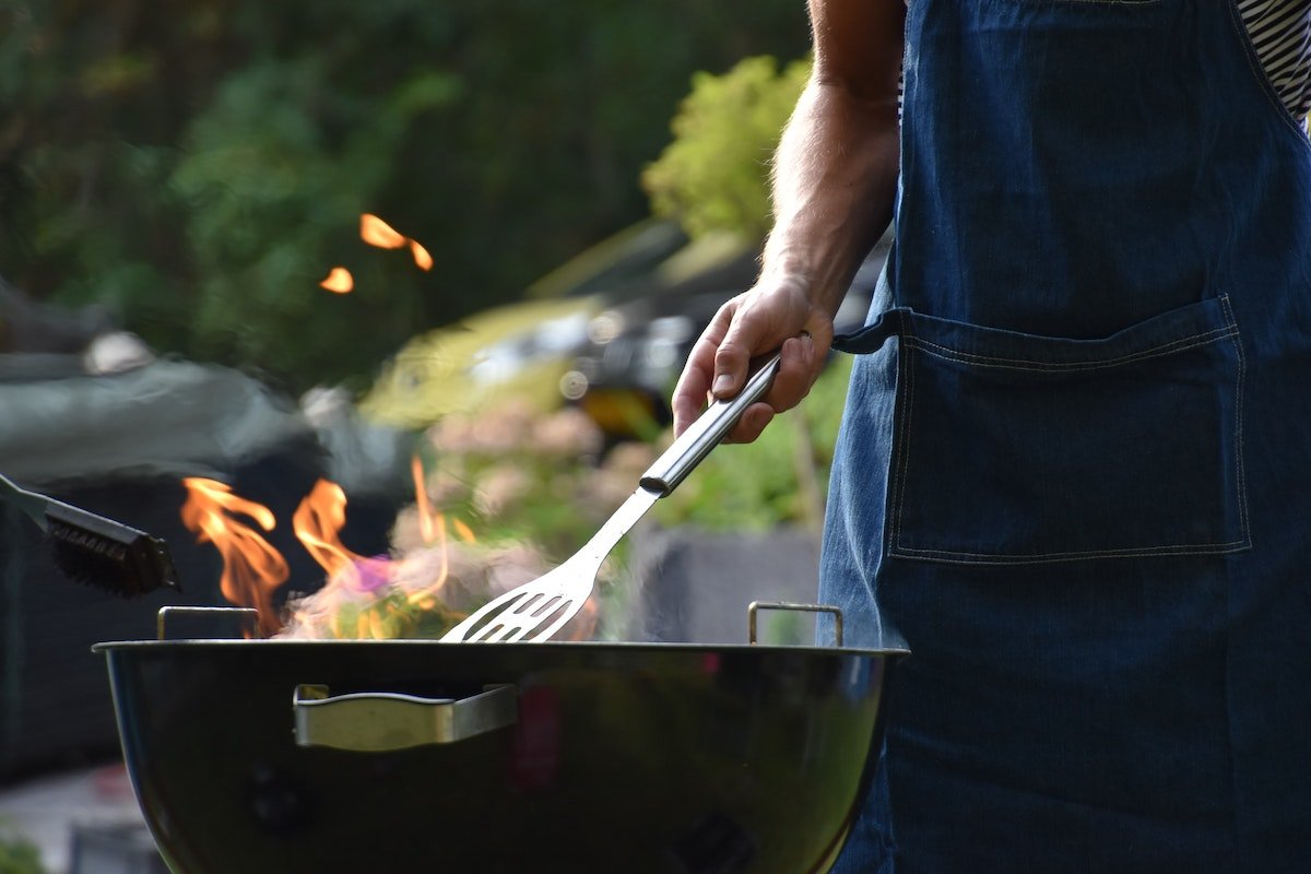 man cooking on a charcoal grill