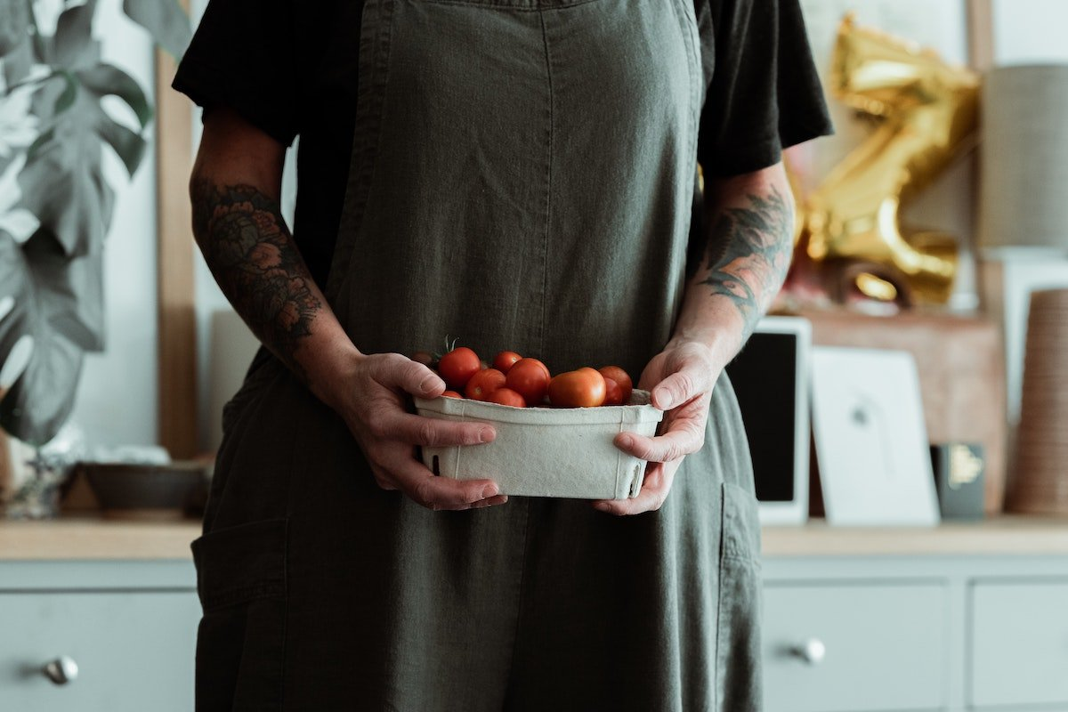 middle-aged woman holding bowl of cherry tomatoes