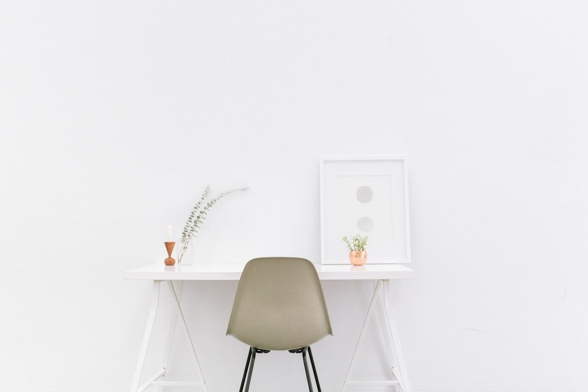 simple white desk with two small plants on it