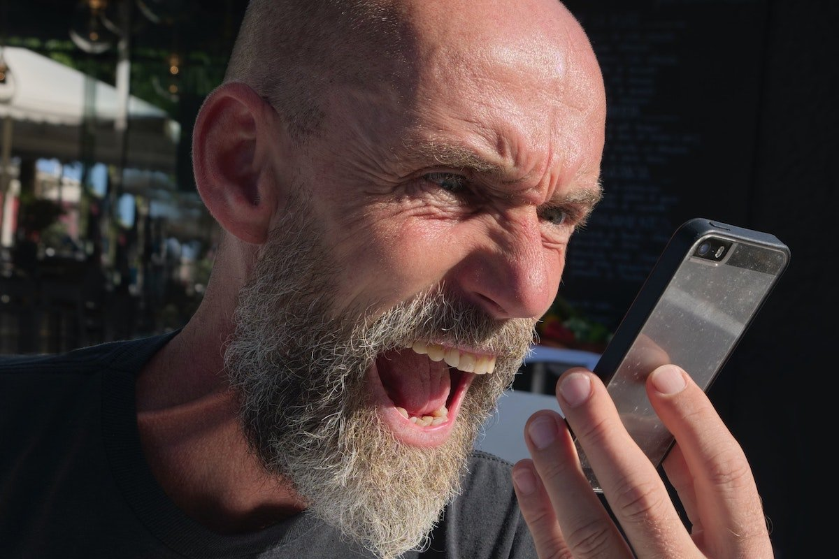 morally questionable man with beard screaming into cellphone
