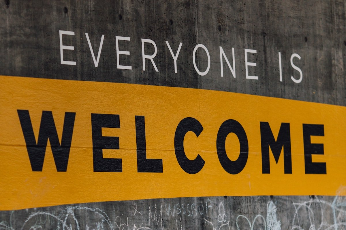 Everyone Is Welcome sign on concrete wall