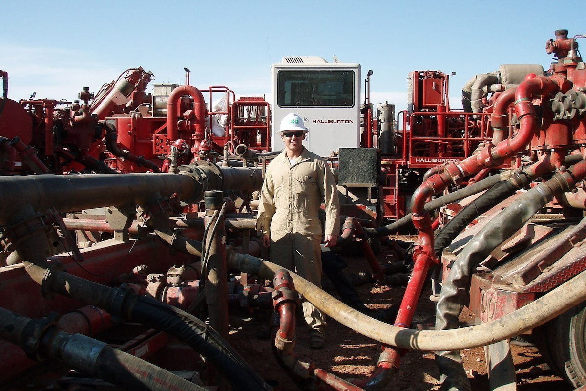 man standing in the midst of natural gas fracking equipment