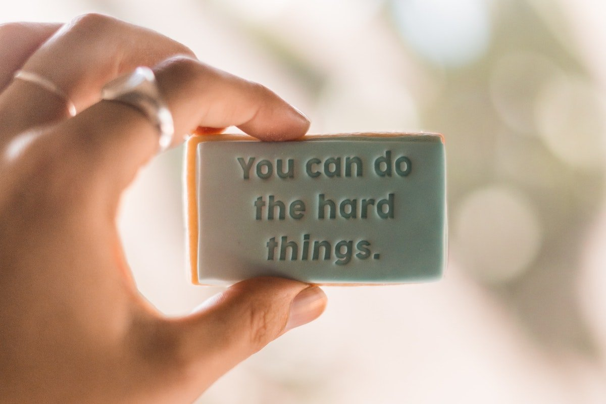 person holding sign that says you can do hard things