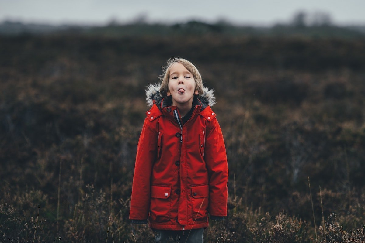 girl in a red coat being unkind by sticking out her tongue