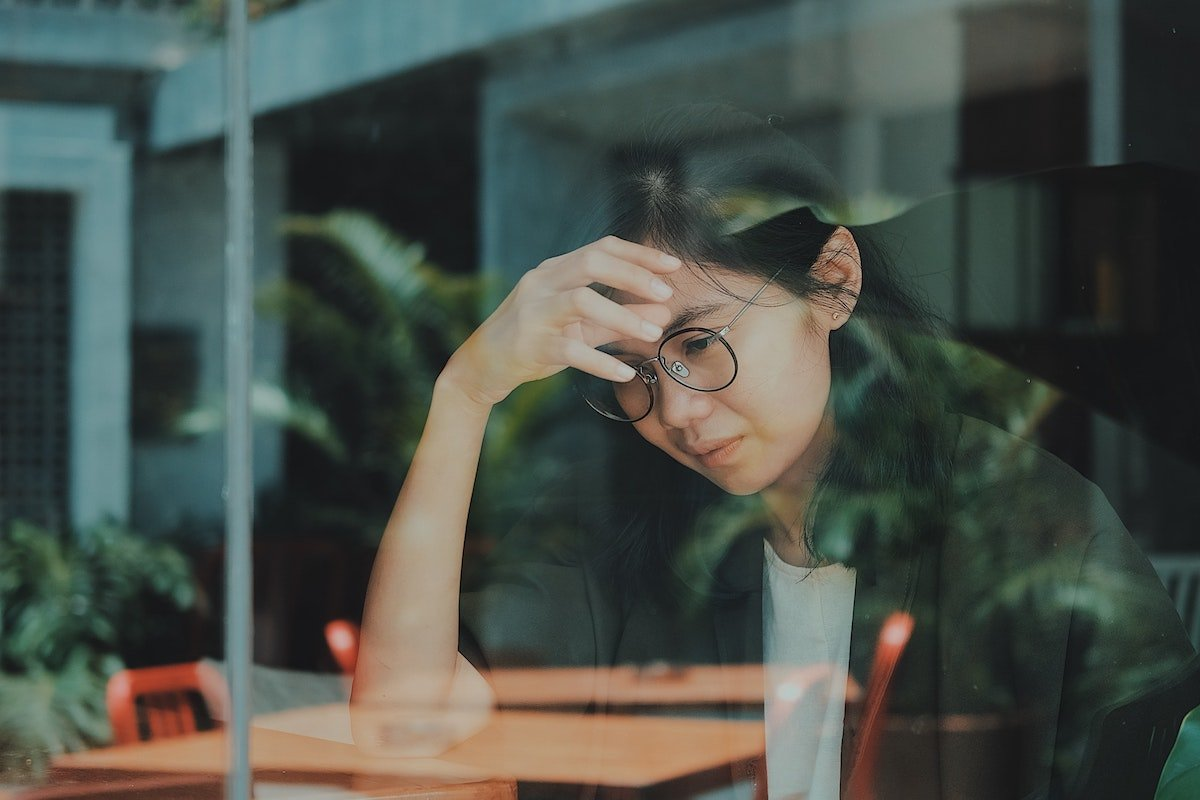 woman in a cafe feeling overwhelmed by life