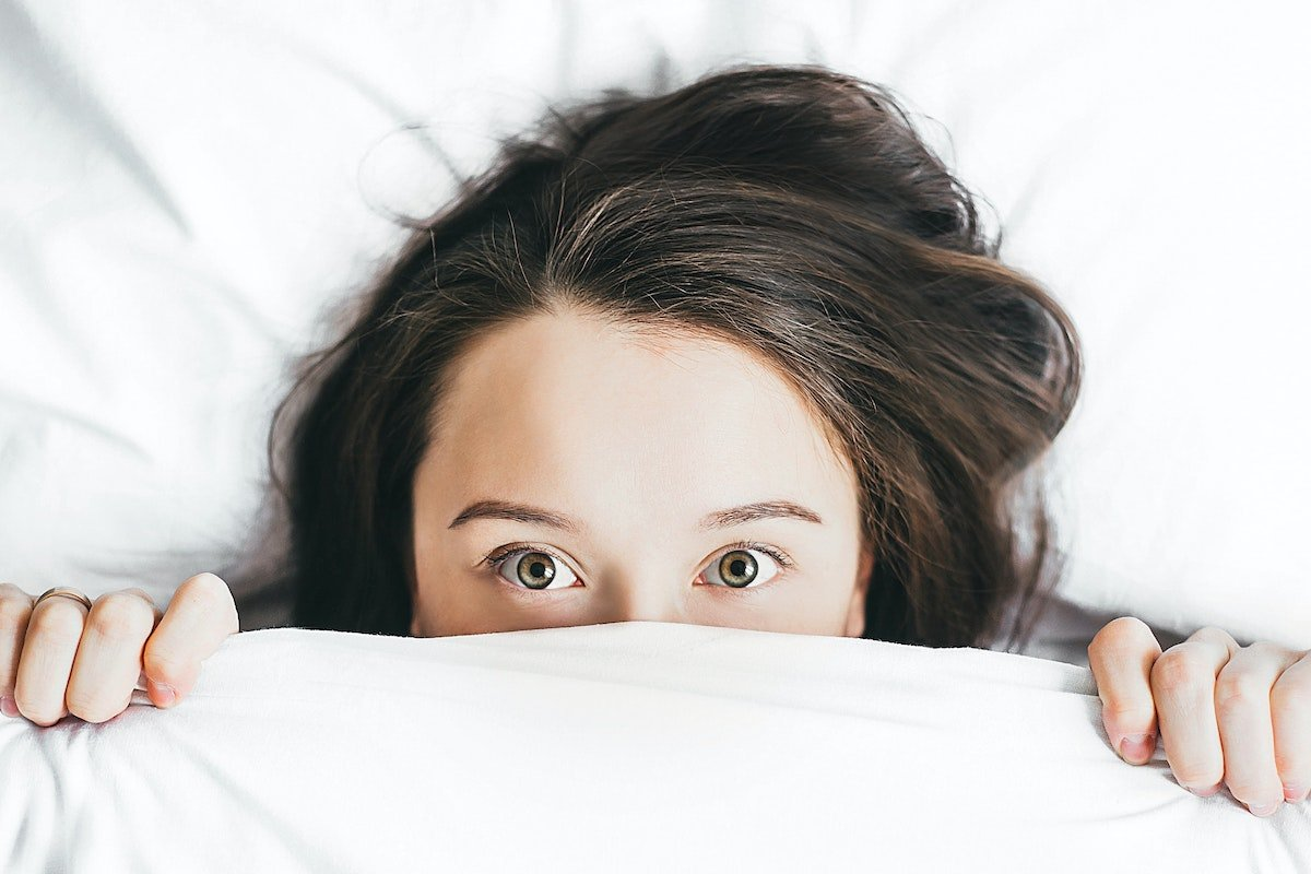 woman hiding under the sheets in fear