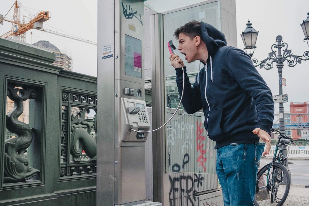 angry mean wearing a hoodie shouts into a pay phone
