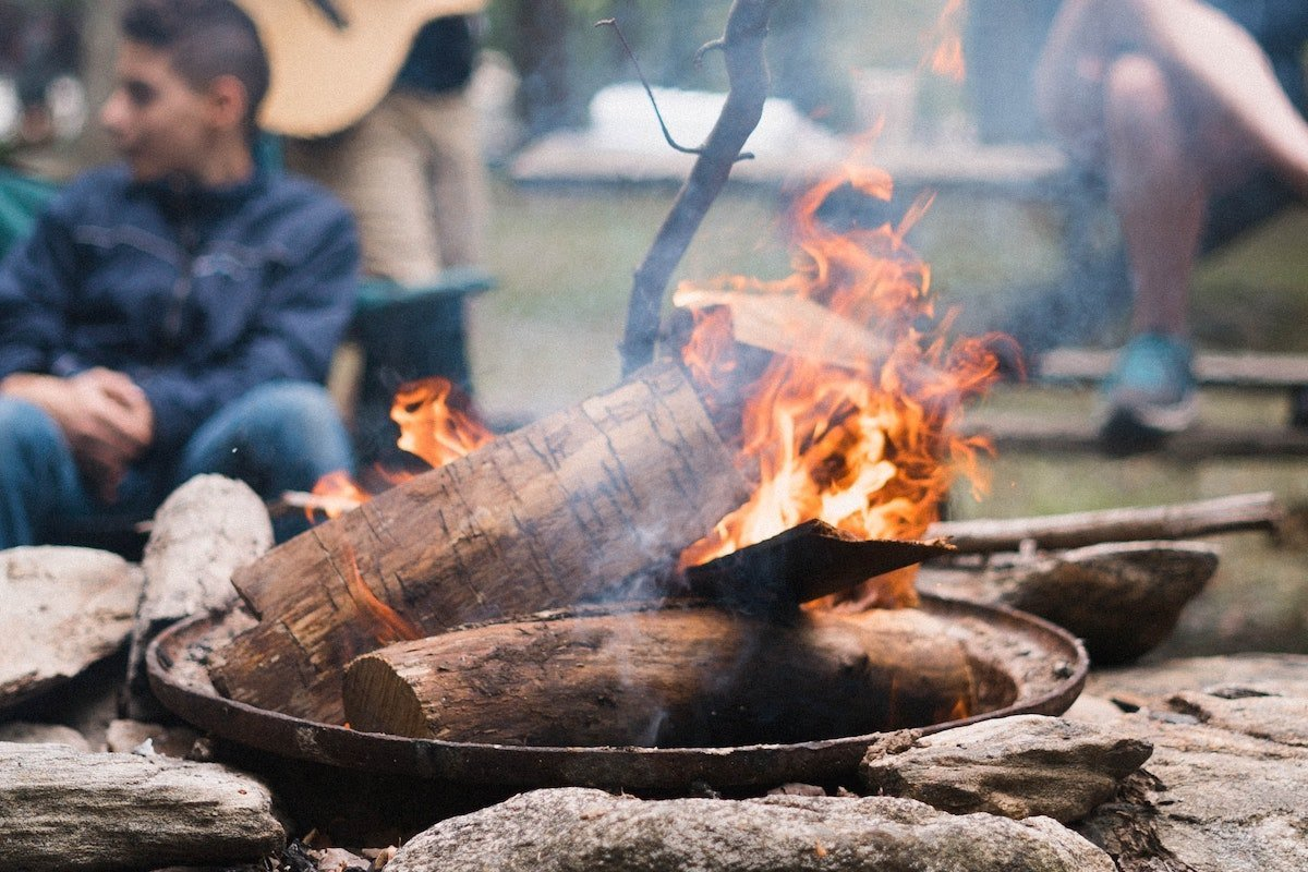 young people sitting around a campfire