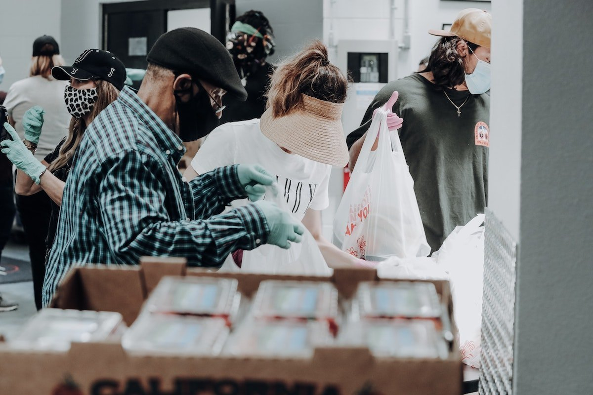 people doing good by volunteering at a food distribution center