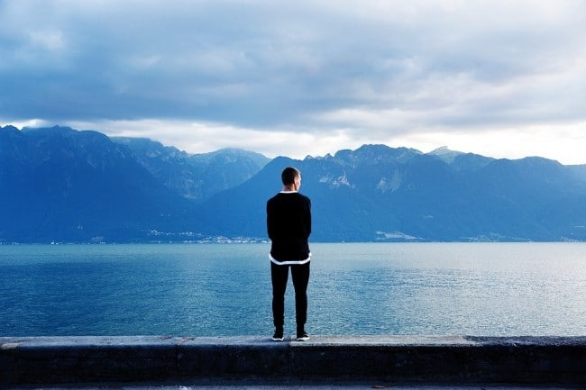 man standing in solitude beside a lake contemplating the end of violence