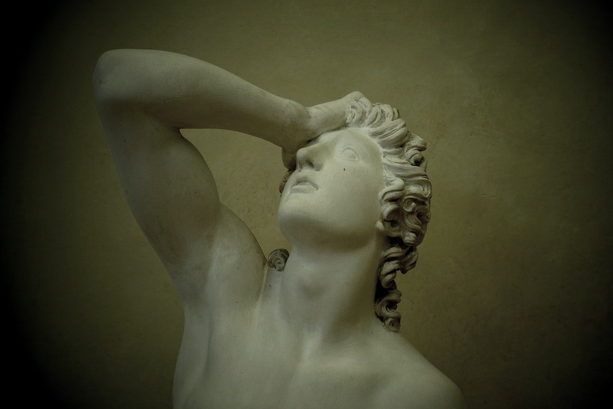 statue of man with hand on his forehead like he's dealing with regret
