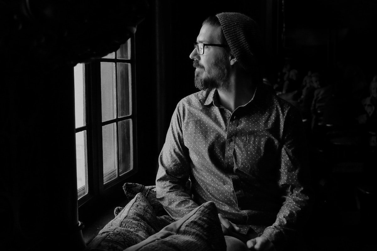 b&w photo of a young guy looking out a window deep in thought