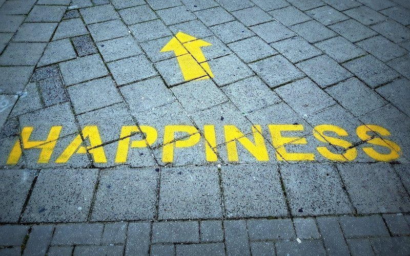 happiness sign on a brick sidewalk